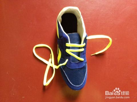 将鞋带穿入左边离自己最近的横线的孔里,再由内而外隔开一个孔穿出图片