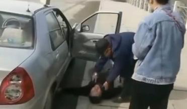 男子躺地上拽着车轮哭天抢地