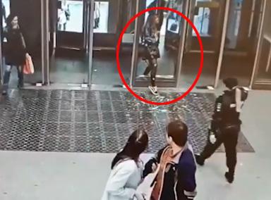 女子低头玩手机撞上玻璃门