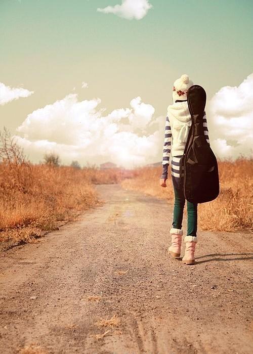 一个女孩背着黑色的吉他包的背影