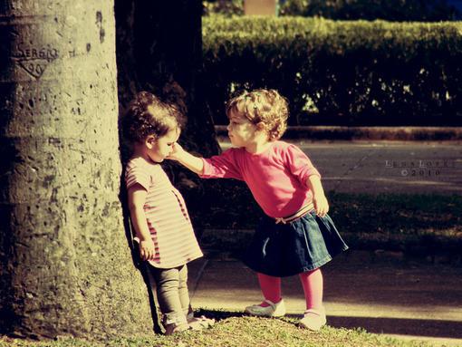 内容是一个可爱的小男孩捏住一个小女孩