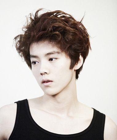 男生将自然卷发烫成更大的卷,梳理成无刘海凌乱美的中短卷发发型,环绕图片